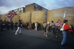 Peace walls in Belfast: Loyalist residents of Belfast holding UK flags march past a peace line