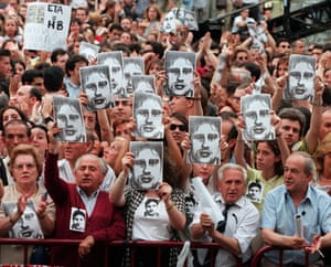 History of ETA: 1997: Spaniards in Madrid hold up pictures of Miguel Angel Blanco Garrido
