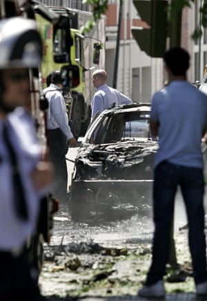 History of ETA: 2005: People stand beside a burnt out car after an explosion in Madrid