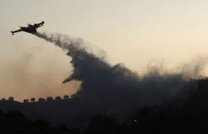 24 hours: A fire-fighting airplane drops water over a forest fire in greece