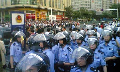 In this image provided by un-named citizen, police assemble opposite protestors in Urumqi.