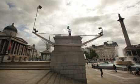 Rachel Wardell stands on the empty fourth plinth in Trafalgar Square in London.