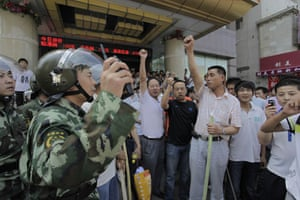 Urumqi riots: Armed police try to stop Han Chinese vigilantes taking to the streets