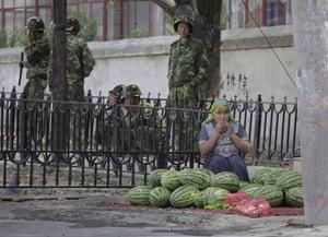 Urumqi: A woman sells fruit near soldiers