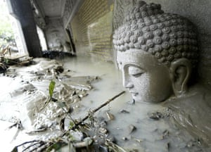 Typhoon Morakot aftermath: Buddha statue is partially submerged in mud in Taiwan