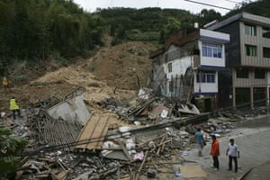 Typhoon Morakot aftermath: People look at the remains of houses which were crushed by a landslide