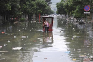 Typhoon Morakot aftermath: A local cycles through a flooded street in Wenzhou, Chjina