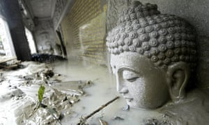 Buddha statue is partially submerged in mud after Typhoon Morakot in Taiwan