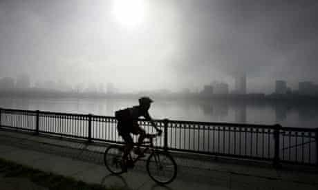 A cyclist rides along the Charles River as the fog lifts from the Boston skyline.
