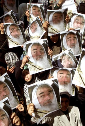 Israel-Palestine timeline: 2004. Palestinian refugees hold posters of Hamas Leader Sheikh Ahmed Yassin