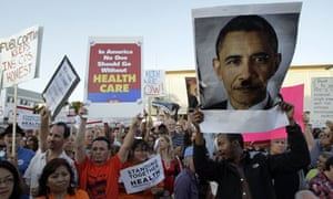 Protester holding a doctored poster of Barack Obama