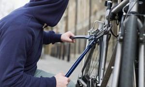 A hooded thief stealing a bike