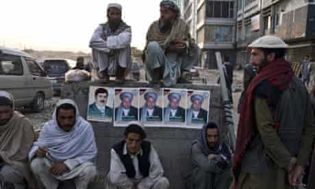 Afghans sit on a block plastered with electoral posters in Kabul.