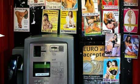 Prostitutes' calling cards in a telephone box in London.