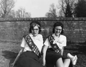 Girl guides 100th: 1959: Girl scouts sitting on the grass by brick wall