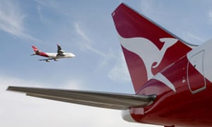 A Qantas 767 passenger jet flies over Sydney Airport