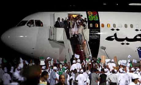 Abdelbaset al-Megrahi (left, in dark suit) arrives at Tripoli airport