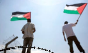 Protesters wave Palestinian flags during a protest in the West Bank.