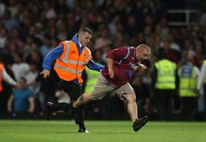 West Ham v Millwall: A steward chases a West Ham United fan