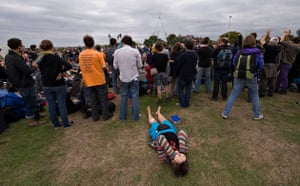 Camp for Climate Action: A protestor covers her face as opening speeches are made on Blackheath