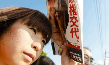 A woman listens to Japan's main opposition Democratic party of Japan leader Yukio Hatoyama