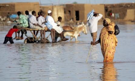 A Sudanese woman walks through a flooded road following heavy rain in southern Khartoum.