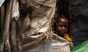 An internally displaced girl peers out of her home in the Mugunga camp in Congo