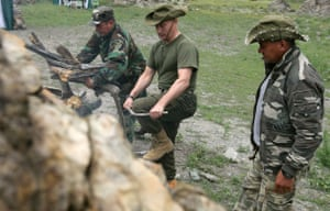 Putin on vacation: Russian Prime Minister Vladimir Putin breaks branches for a fire