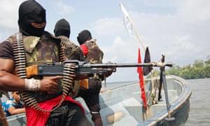 Separatist rebels brandish weapons on the Escravros River in the Niger Delta