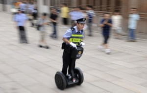 24 hours in pictures: A policeman uses a Segway to patrol a street in China