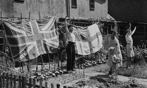 A family displays an English and a British flag in their back garden during the second world war.