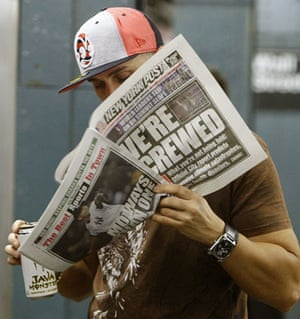 Climate Week in New York: A man reads a fake edition of the New York Post on a subway platform