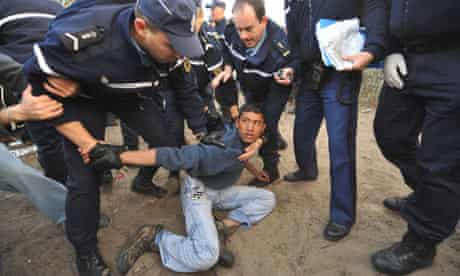 French police detain a migrant at a camp called the jungle near Calais