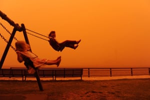 Sydney dust storm: Six-year-old Ariella and her three-year-old sister Romy enjoy a swing