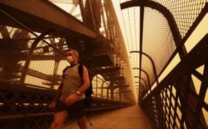 Sydney dust storm: A man wearing a dust mask walks across the Sydney Harbour bridge