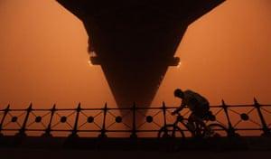 Sydney dust storm: A cyclist rides under the Sydney Harbour bridge