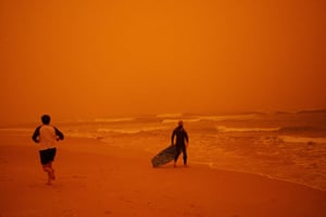 Sydney dust storm: A surfer heads for the water at Bondi Beach