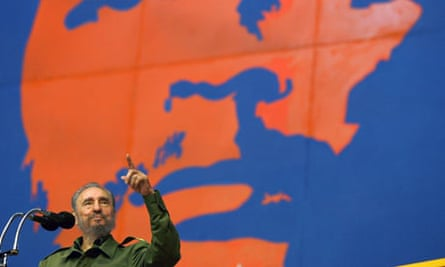 Cuban President Castro acknowledges applause while standing underneath Che Guevara image in Havana