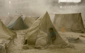 Dust storm: Afghan refugee child hides from a dust storm