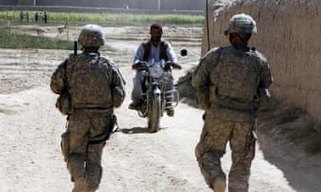 Afghan man rides his motorcycle while US soldiers search for IEDs