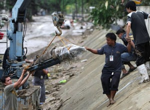 Philippines floods: Rescuers use a crane to recover the body of a flood victim in Marikina City
