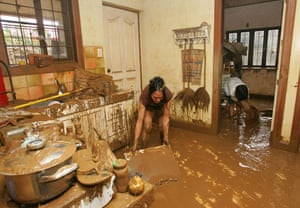 Philippines floods: Women scrape mud from the floor after the floodwaters subside in Marikina