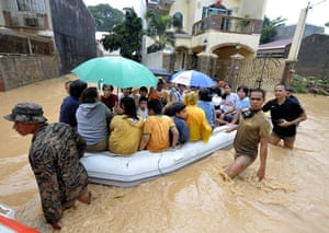 Philippines floods: Rescues use a boat to help Filipino residents trapped by floods