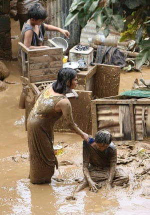 Philippines floods: Filipinos are drenched in mud as they recover belongings from damaged homes
