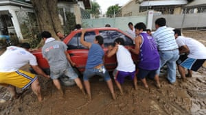 Philippines floods: A group of men attempt to move a car as flood waters recede
