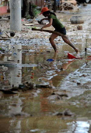 Philippines floods: A girl crosses a muddy road as flood waters recede in Marikina City