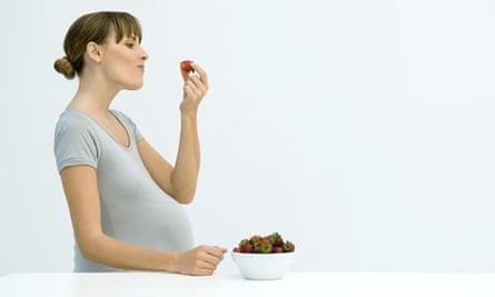 Pregnant woman eating strawberries
