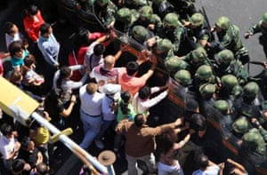 Han Chinese protestors push against security forces in Urumqi, Xinjiang