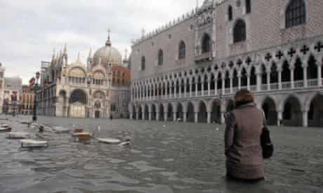 Woman walking in flooded Piazza San Marco