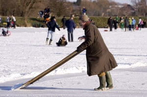 Skating on the fens: Clearing away the loose snow to make a smoother surface to race on